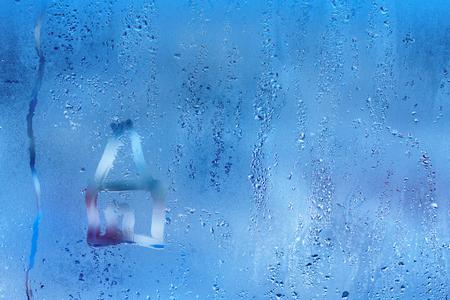 Mão desenhar no vidro e a gota de água. Condensação e pingos de chuva em uma janela, profundidade de campo rasa.