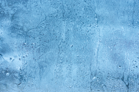Frozen glass of the window from the inside of the room. Background in a cool tone with a texture of dripping water drops