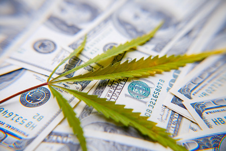 Money with marijuana leaf close up, high quality. Sheet lies on background of one hundred US dollars. Thematic photos of hemp and cannabis