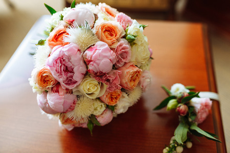 Wedding bridal bouquet with roses and other flowers on the table