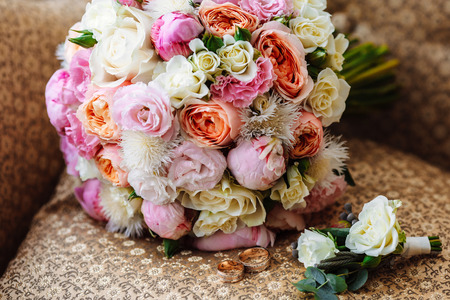 Beautiful wedding bouquet, two gold rings, boutonniere, lying on the armchair, wedding day. Important holiday accessories
