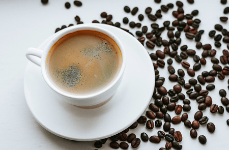 White cup with fresh coffee on saucer close up with grains of coffee on white isolated background