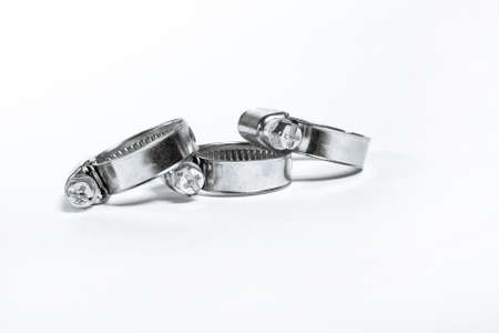 New metal hose clamps with threaded connection for pipes, stainless steel, small size on isolated white background close-up