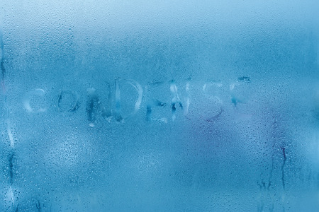 The inscription condenses on glass close-up with condensation. Background with water drops. High humidity indoor