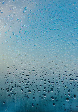 Strong humidity in wintertime. Water drops from home condensation on a window. Misted glass background 免版税图像