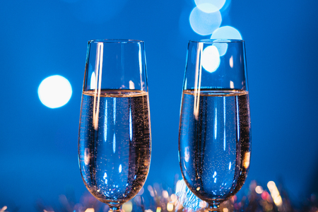 Glasses with champagne against fireworks and holiday lights - Celebrating the New Year Stockfoto