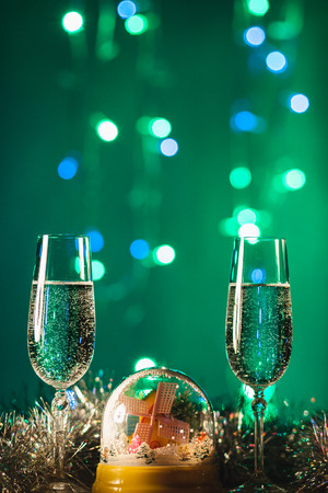 Glasses with champagne Christmas balls against holiday lights - New Year background