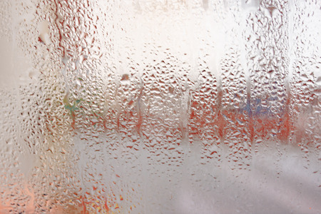 Background of the condensate flowing water on the window glass Imagens