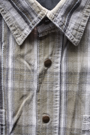 Close up part of a shirt from hemp fabric. Casual man's shirt with pattern. Wrinkled texture from hemp and cotton background