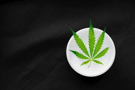 Top view of a jar with CBD or hemp salve with cannabis leaf on black background. Marijuana cream. Cannabidiol topicals concept with copy space