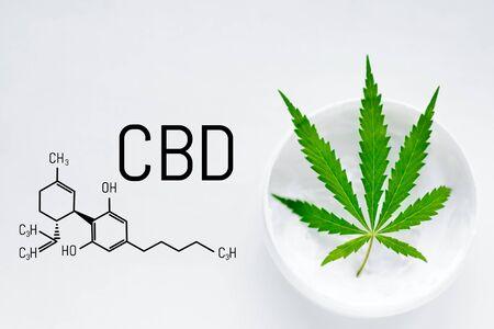 CBD-Cannabiscreme mit grünem Marihuana-Blatt. Molekulare Struktur medizinische Chemie Formel Cannabis der Formel CBD Cannabidiol. Naturkosmetik mit Hanfextrakt auf weißem Hintergrund Standard-Bild