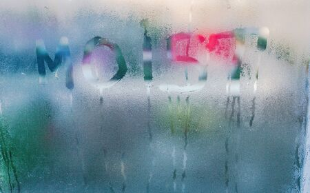 Moist word written on wet window. High level of dampness in apartment. Window glass with high air humidity. Background of natural water condensation Stock Photo