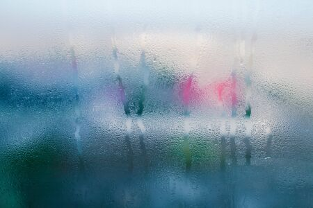 Moist word written on wet window. High level of dampness in apartment. Window glass with high air humidity. Background of natural water condensation Banco de Imagens