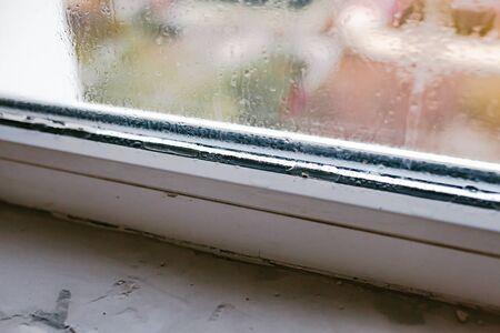Palabra húmeda escrita en ventana mojada. Alto nivel de humedad en apartamento. Vidrio de ventana con alta humedad del aire. Fondo de condensación de agua natural