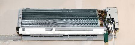 Air conditioning service, repair and maintenance concept. Closeup at an indoor unit. Radiator with copper tubes and plates. Technician fixing air conditioner indoors. Disassembled conditioner