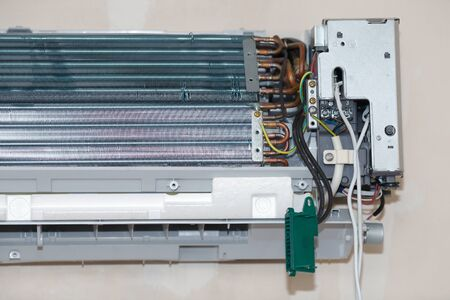 Air conditioning service, repair & maintenance concept. Specialist cleans and repairs the wall air conditioner. Picture technician cleaning coil cooler of air conditioner Banco de Imagens