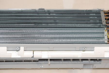 Concept of repair and maintenance of air conditioners. Radiator detail with copper tubes and plates. Fixing the air conditioner in the room. Dismantled air conditioning. Close up of indoor unit
