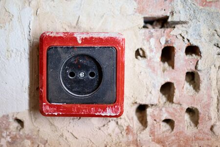 EU power outlet type C, electric point of power at home, on a red brick background with holes Banco de Imagens