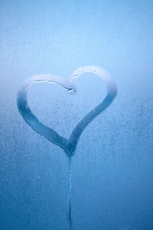 Hand drew heart on glass with drops of condensed steam with drops of water. Hot water vapor condenses on the cold glass in the bathroom. Close up detail of moisture condensation problems Stockfoto
