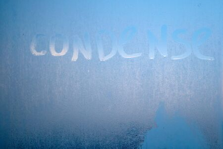Inscription condense on glass with drops of condensed vapor with drops of water. Close up detail of moisture condensation problems. Hot water vapor condenses on the cold glass in the bathroom