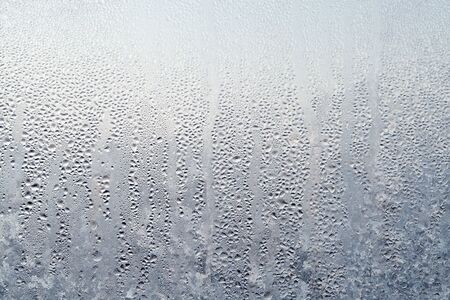 Texture of Frozen drops of condensed steam water drops on the transparent window glass. Clean background. Water vapor condenses on cold window glass and freezes into ice