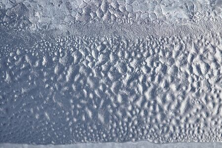 Frozen drops of condensed steam water drops on the transparent window glass. Clean background. Condensation of moisture at extreme temperatures. Water vapor condenses on cold window glass and freezes Stockfoto