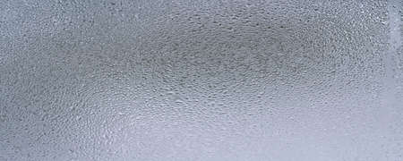 Abstract background with detail of moisture condensation problems, hot water vapor condensed on the cold glass close up water drop on blurred background
