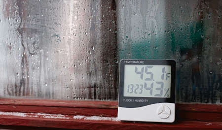 Measurement of air temperature, dew point, humidity with a device (hygrometer), against a background with condensation on the glass, high humidity