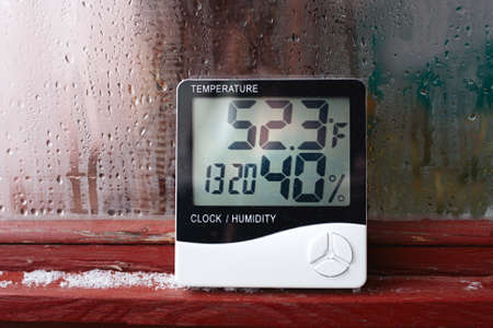 Electronic clock, calendar, thermometer, and hygrometer, against the background of condensation on glass, high humidity. Digital hygrometer in the laboratory shows the temperature of the pharyngeite