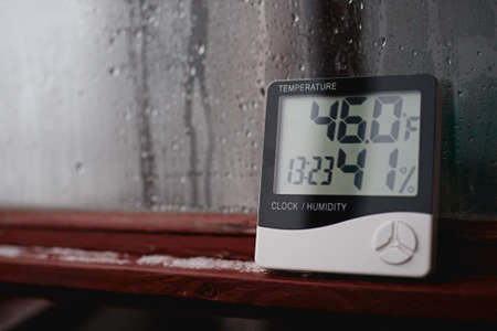 Measurement of air temperature, dew point, humidity with a device (hygrometer), against a background with condensation on the glass, high humidity 版權商用圖片