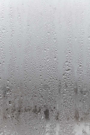 Natural drops of water flow down the glass, high humidity in the room, condensation on the glass window. Neutral colors. Excellent background with condensation drops texture. Vertical photo orientation