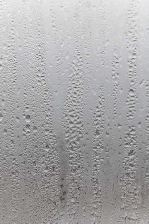 Close up water drop on gray background, misted glass with droplets of water draining down. Dripping Condensation