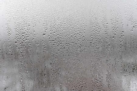 Natural drops of water flow down the glass, high humidity in the room, condensation on the glass window. Neutral colors. Excellent background with condensation drops texture. Horizontal orientation of the photo