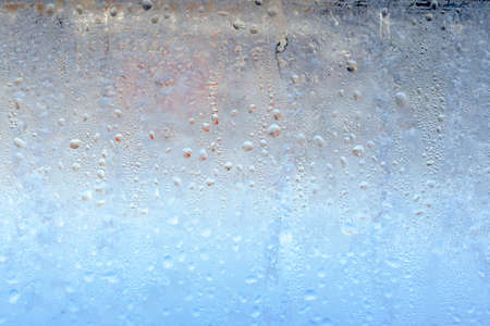 The texture of frozen drops of condensation on a transparent glass window. Water drops. Rain. Abstract texture background. A sharp cold snap, a frozen drop of water on the glass in winter 版權商用圖片