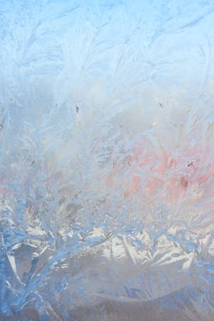 Vertical image of a winter background on a transparent glass window with a frozen texture. Abstract texture background, vertical photo, copy space for your design or text