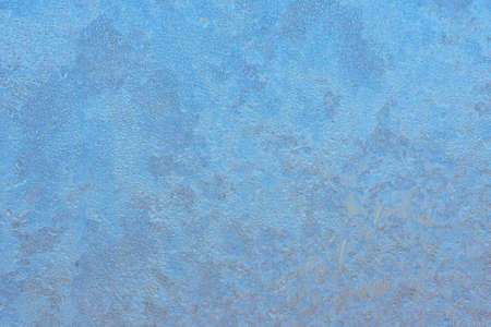 Winter background on a transparent glass of a window with a frozen texture. Abstract texture background, horizontal image, copy space for your design or text