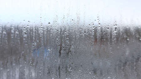 Background of condensation of water droplets on glass, humidity and fog behind glass, bad weather, rain Stock Photo