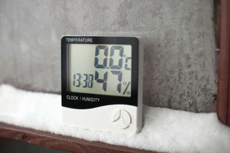 Measurement of the temperature and humidity, thermometer and hygrometer on a window with snow on the background of frozen glass