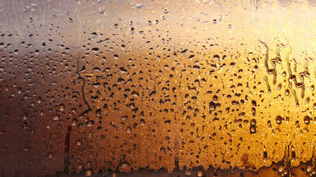 Drops condensation on the clear glass window. Water drops. Abstract background texture, condensation on the glass with dripping drops