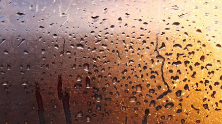 Horizontal natural background with water drops on the window with sunbeams, condensation on the glass with dripping drops