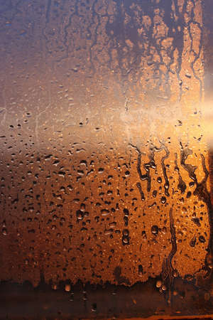 Vertical natural background with water drops on a window with sun rays, condensation on glass with dripping drops