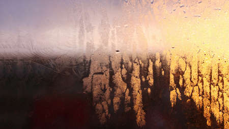 Drops of condensate on the sweaty glass window. Cold foggy glass. Wet window background, texture condensation with dripping drops Фото со стока