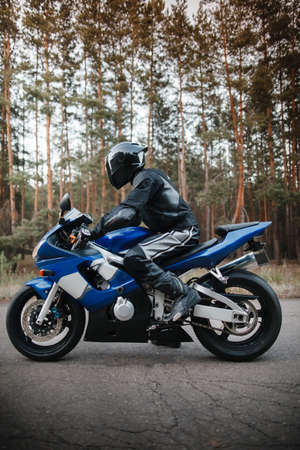 Motorcyclist in leather protective suit and black helmet sits on sports motorcycle. Biker in black rides on the road against the background of the forest. Side view