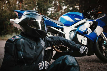Biker in black protective suit and helmet sits next to his with a sports motorcycle on the road