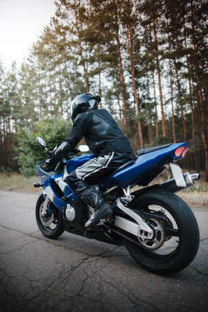 Rear view of motorcycle driver driving in helmet with blurred forest background