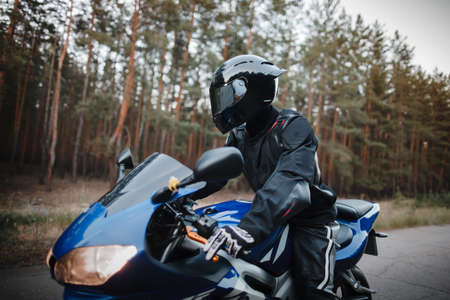 Motorcyclist in leather protective suit and black helmet sits on sports motorcycle. Biker in black rides on the road against the background of the forest Фото со стока