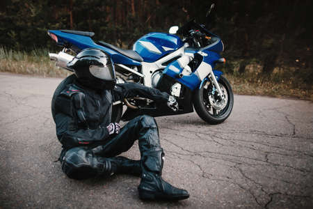 Biker in a protective suit and a black helmet sits next to his motorcycle on the road. Motorcyclist resting near a motorcycle Фото со стока