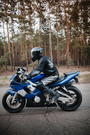 Biker in black protective suit and helmet sits on his sports motorcycle