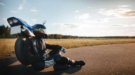 Motorcyclist or biker in black leather jacket and safety helmet sits near a sports motorcycle on the road and looks at the sunset sky with copy space