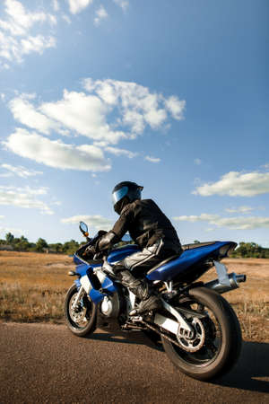 Biker or motorcyclist in a black leather suit and helmet sits on a sports motorcycle and looks into the distance. Vertical photo orientation
